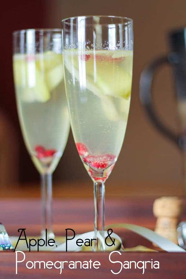 Apple Pear and Pomegranate Sangria in two champagne flutes