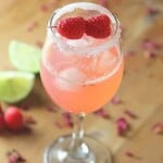 raspberry rosewater gin rickey in glass with lime in background