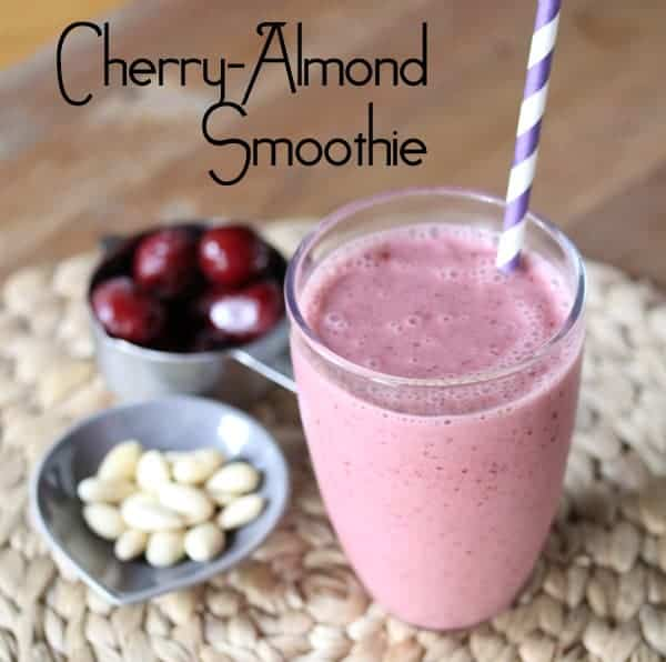 Cherry Almond Smoothie in a glass with fresh cherries and almonds next to it