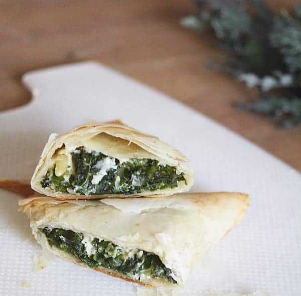 Close up view of Kale Spanakopitas cut in half to see the kale and cheese inside