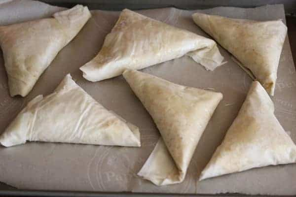 Six Kale Spanakopitas wrapped in phyllo pastry on parchment before baking