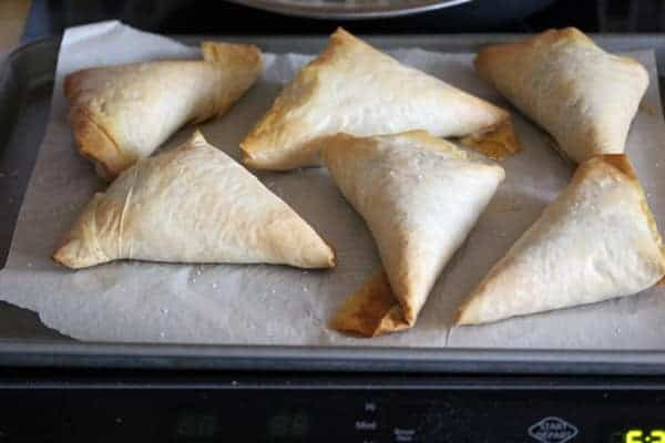 Six Kale Spanakopitas on parchment lined baking pan after baking
