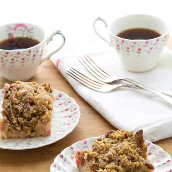 two slices of rhubarb coffee cake with nutmeg and pecan streusel on plates with cups of coffee