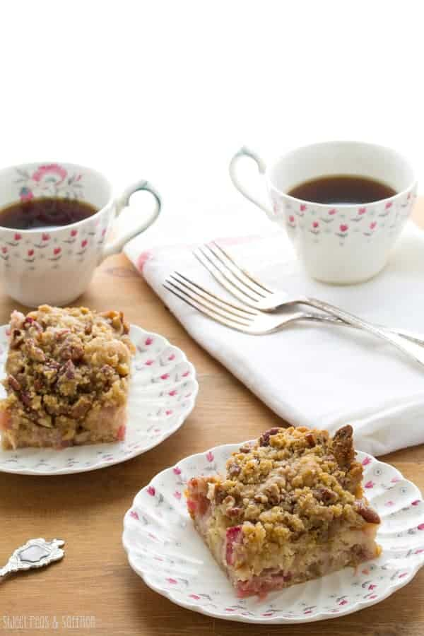 Two pieces of Rhubarb Coffee Cake with Pecan Streusel on plates with cups of coffee behind them