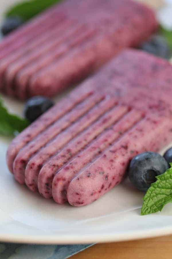 Close up shot of Blueberry Mint Yogurt Popsicleson a white plate
