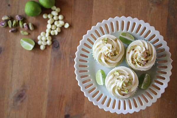 Three Key Lime Cupcakes on a cake stand with white chocolate chips, pistachios, and limes on the side