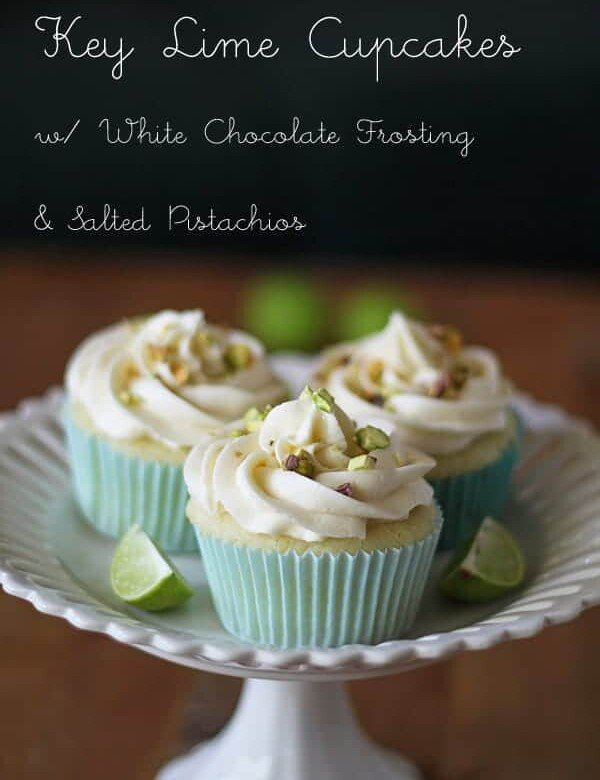three key lime cupcakes with white chocolate frosting and salted pistachios on white plate