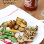 sriracha and sesame glazed pork tenderloin on plate with potatoes and vegetables