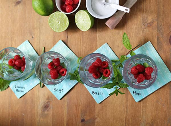Overhead view of four glasses of Raspberry Smash Cocktail with four herb options of lemon balm, sage, basil, or mint
