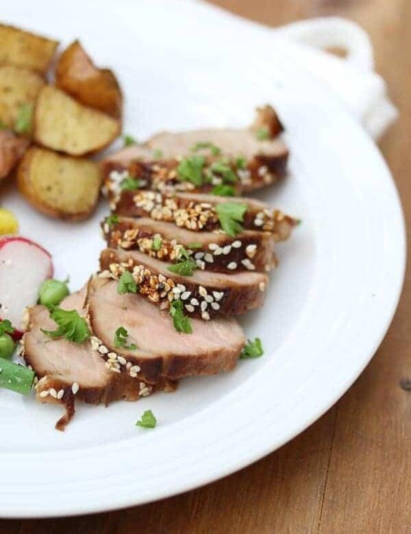 sriracha and sesame glazed pork tenderloin on plate with potatoes and vegetables