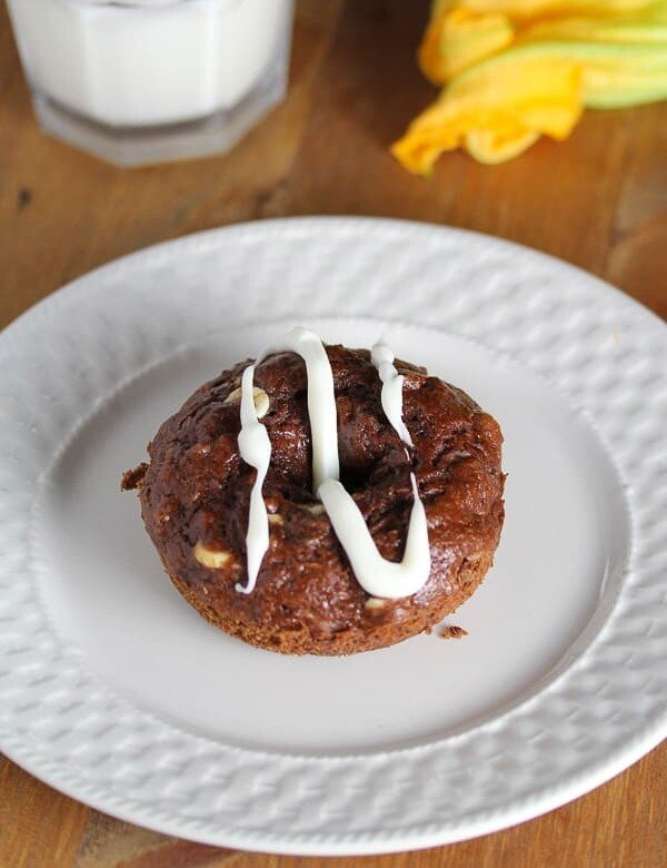 chocolate and zucchini baked donuts with white glaze on white plate