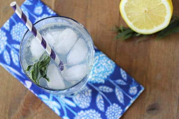 Overhead shot of Lemon Tarragon Spritzer in a glass with a striped straw and half lemon