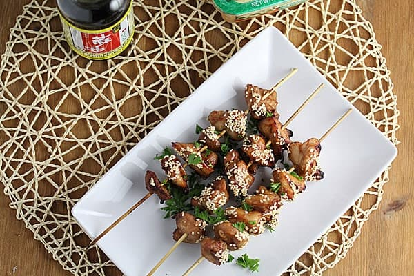 Three Grilled Chicken Kebabs on white serving tray with sesame seeds