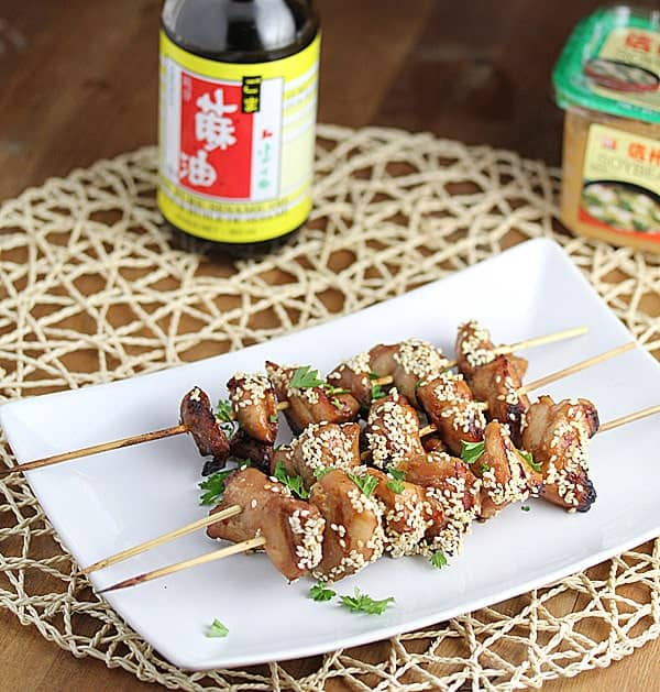 Grilled Chicken Kebabs on white serving plate with bottle of soy sauce and miso paste in the background