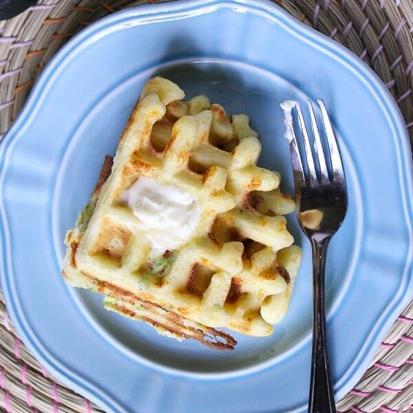overhead shot of zucchini cheddar and cornmeal waffle on blue plate with fork