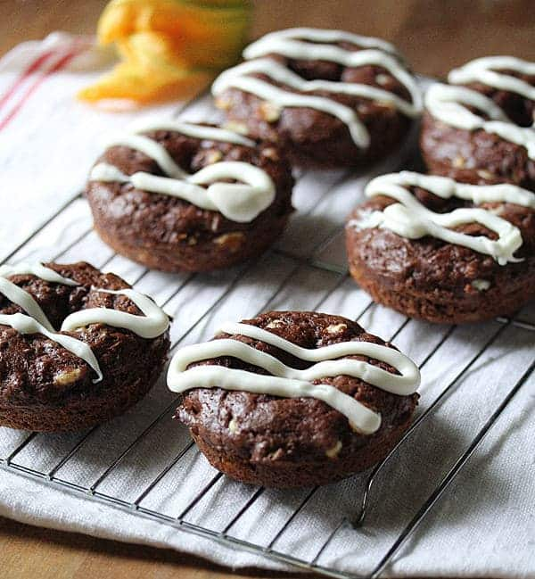 Six Chocolate Zucchini Donuts with white chocolate drizzle cooling on a wire rack