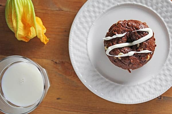 Chocolate Zucchini Donut with white chocolate drizzle on a white plate with a glass of milk