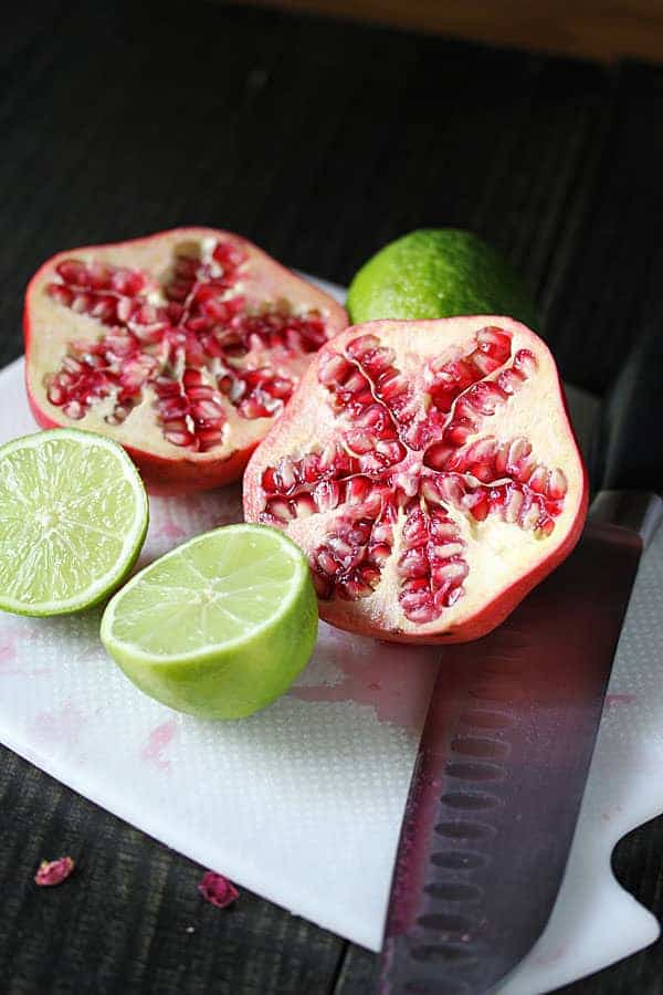 Fresh pomegranate cut in half with a whole lime cut in half next to it