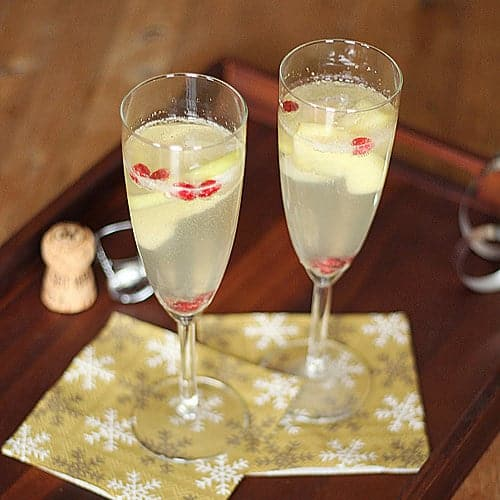 two apple pear and pomegranate sangria glasses on wood tray