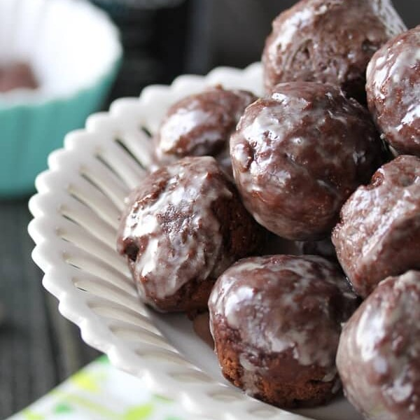pile of guinness chocolate glazed donut holes in white bowl