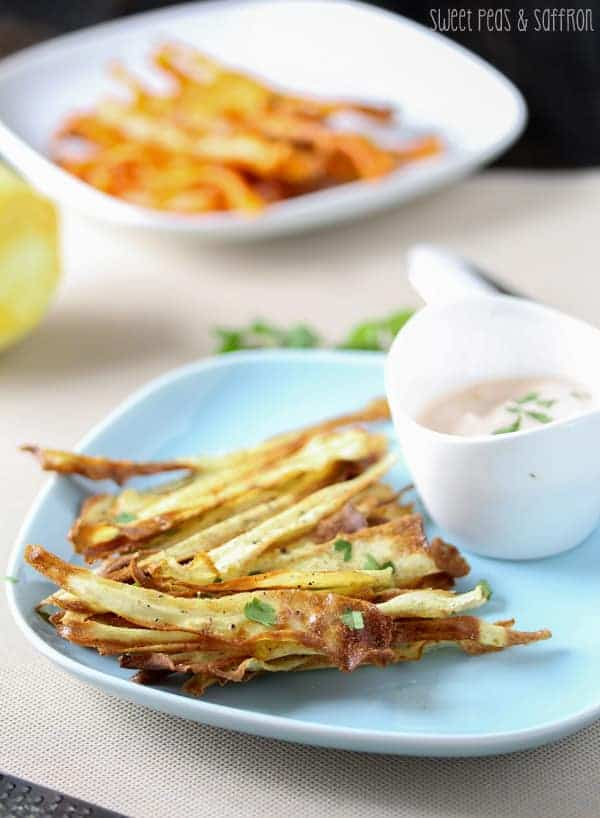 Baked Carrot Chips on a blue plate with Spicy Harissa Yogurt Dip on the side