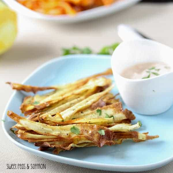 Side view of Baked Carrot Chips on a blue plate with Harissa Yogurt Dip
