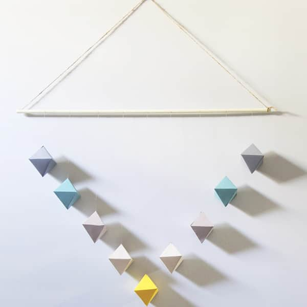 Colorful geometric paper wall hanging on white wall