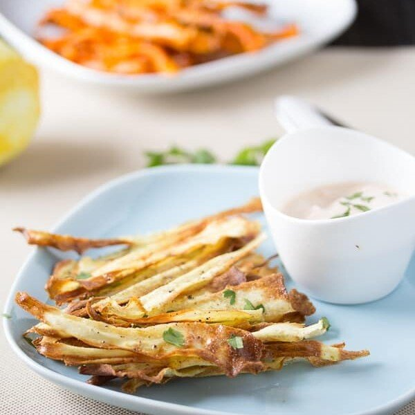 crispy baked carrot hips with spicy harissa yogurt dip in white bowl