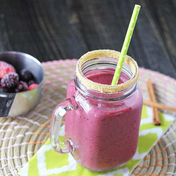 Triple Berry Pie Smoothie in a mason jar with a green straw and cup of berries behind it