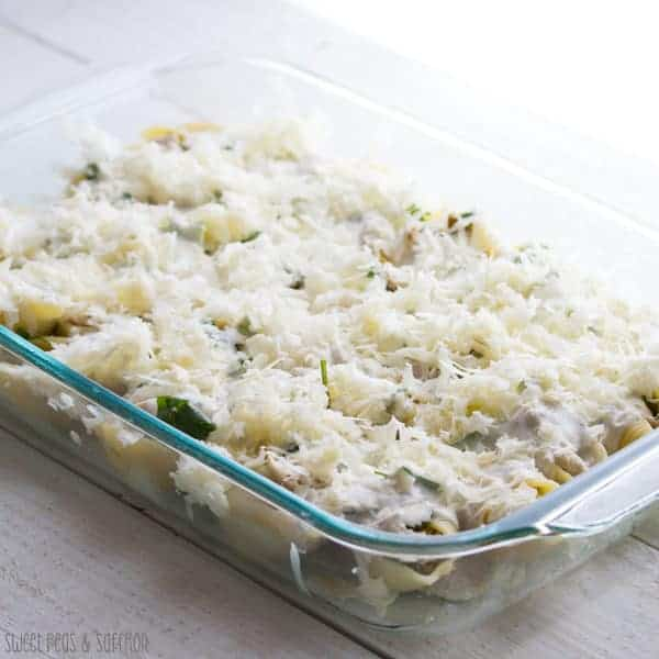 Chicken Stuffed Pasta Shells in baking dish with sauce and cheese on top before baking