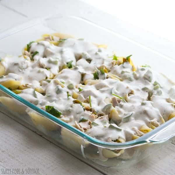 Chicken Stuffed Pasta Shells in glass baking dish with creamy sauce on top