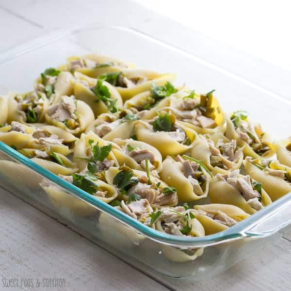 Cheesy Chicken Stuffed Pasta Shells in glass baking dish with fresh cilantro on top