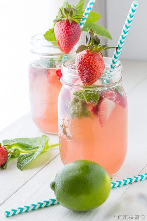 Close up shot of Strawberry Rhubarb Rosé Sangria in a mason jar with a whole lime next to it