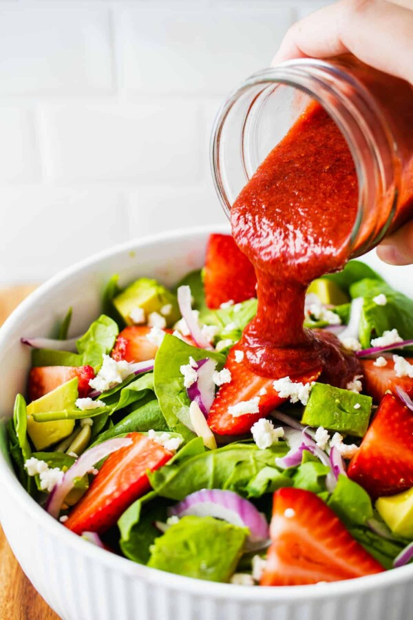 pouring vinaigrette over strawberry spinach salad