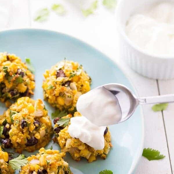 five southwestern baked falafels with corn and black beans on blue plate with spoon putting sour cream on one