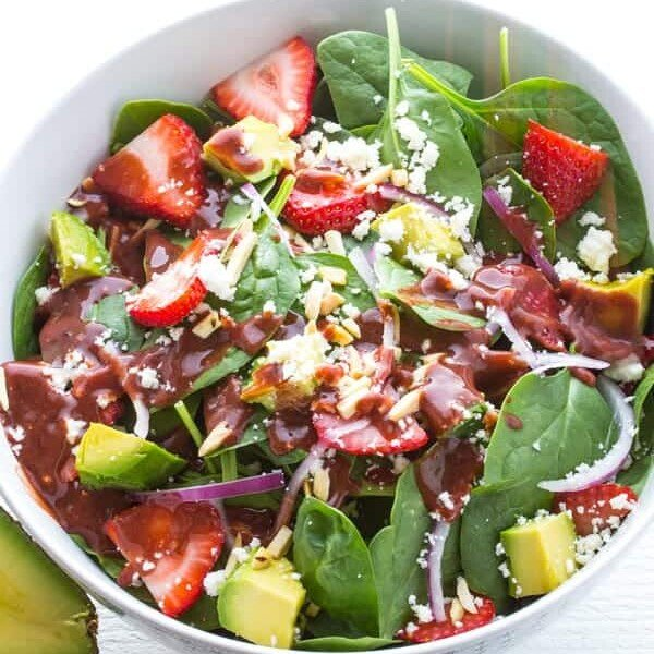 Strawberry spinach salad in a white bowl with strawberry vinaigrette