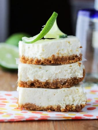 stack of three tequila lime cheesecake bars with lime slice on top