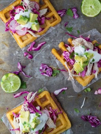 overhead shot of chipotle cornmeal waffle tostadas with chicken and lime crema