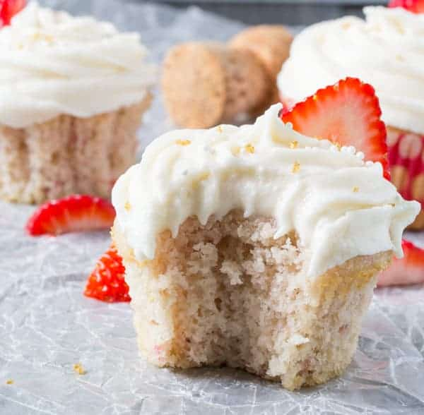 Close up view of Strawberry Cupcakes with a bite taken out and champagne cork in the background