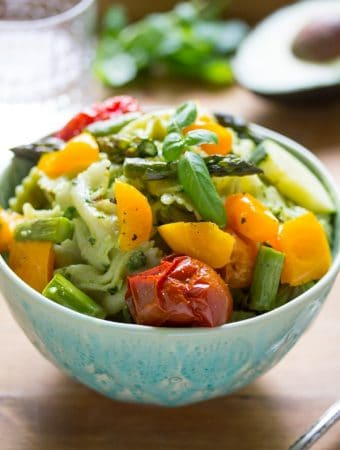 side angle view of avocado pesto pasta salad in a bowl