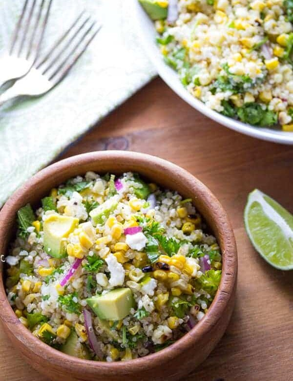 overhead shot of charred corn salad with feta mint and quinoa in wooden bowl with lime wedge
