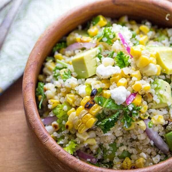 overhead view of charred corn salad with feta, mint and quinoa in large wooden bowl