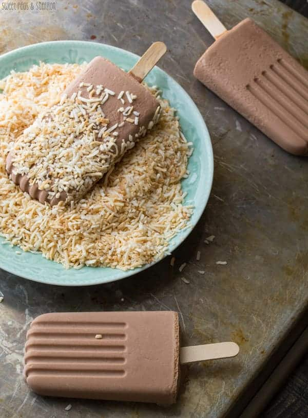 Three Nutella Popsicles with one being dipped in the toasted coconut in blue bowl