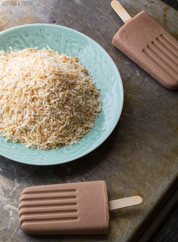 Two Nutella Popsicles laying next to toasted coconut in a blue bowl