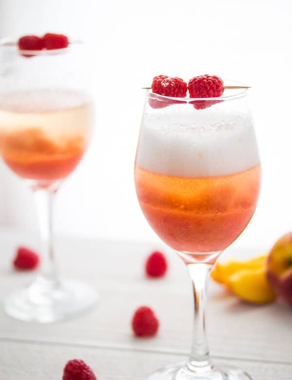 two peach reaspberry bellinis in wine glasses with fresh raspberries
