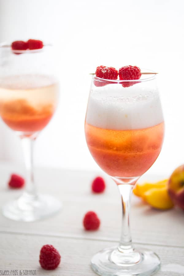 Two glasses of Peach Raspberry Bellinis with fresh raspberry garnish