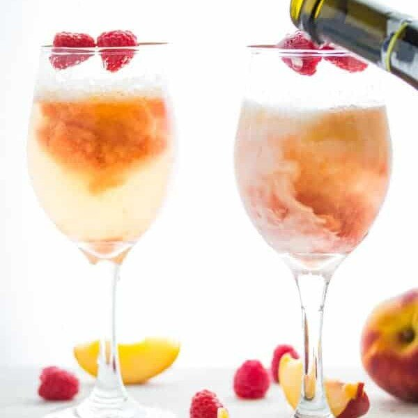 two peach reaspberry bellinis in wine glasses