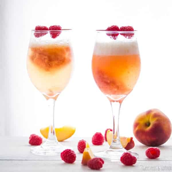 Two glasses of Peach Raspberry Bellinis with a whole peach sitting next to glass