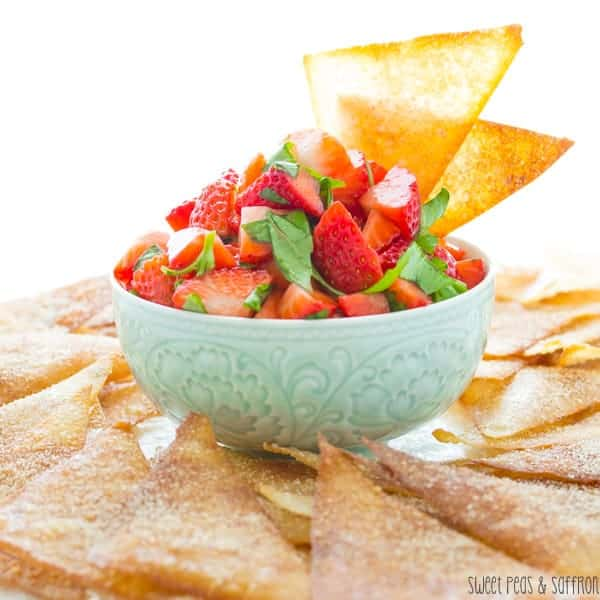 Side view of Strawberry Bruschetta in a blue bowl with two wonton chips