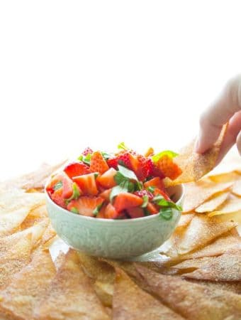 hand dipping a wonton chip into strawberry bruschetta